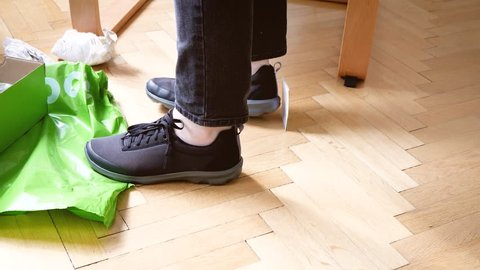 PARIS, FRANCE - CIRCA 2018: Woman testing trying in home environment the new Crocs modern sneakers shoes bought from online fashion store after unboxing