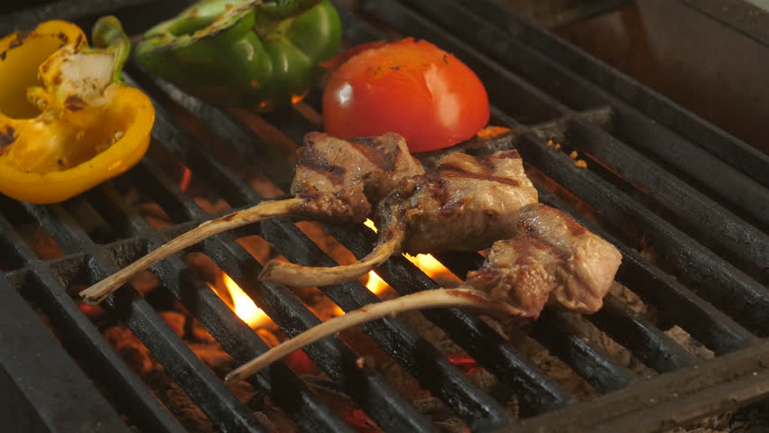 Meat on a bone grilled with vegetables, grilled lamb, grilled peppers, grilled tomatoes, macrobiotic, slow-motion filming