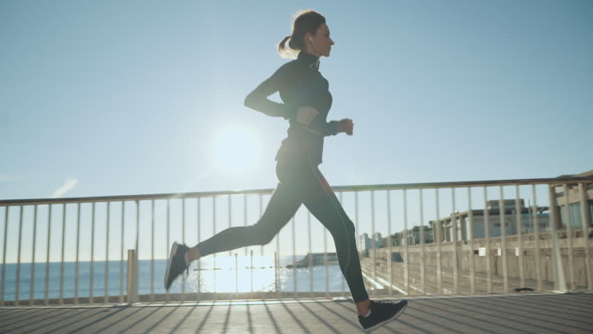 Young sportive woman running near the city beach, athletic girl jogging outdoors in the morning, slow motion #1009706351