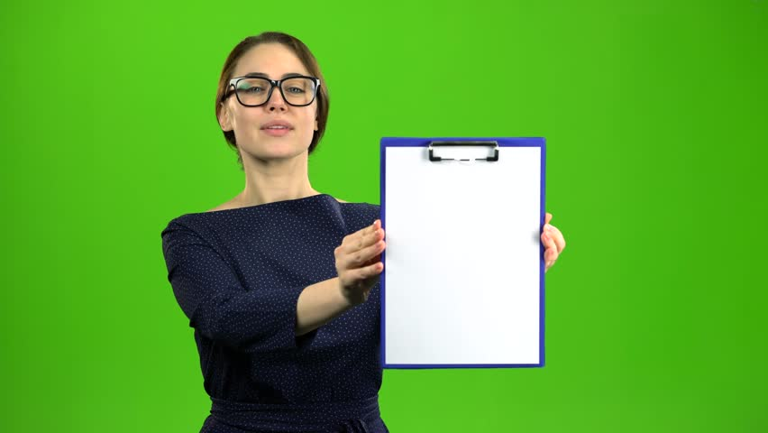 Woman raises a paper tablet and smiles. Green screen