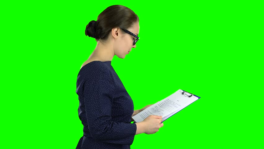 Woman comes with a paper tablet on the street. Green screen. Side view
