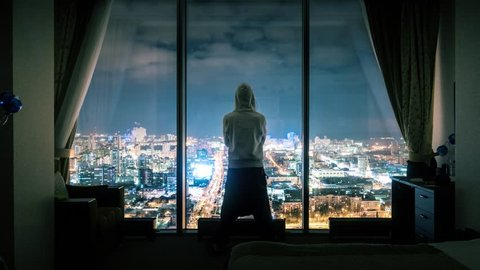 Hooded anonymous man silhouette standing in dark room looking out of panoramic window with illuminated night city view in background. Timelapse, 4K UHD. Zoom in.
