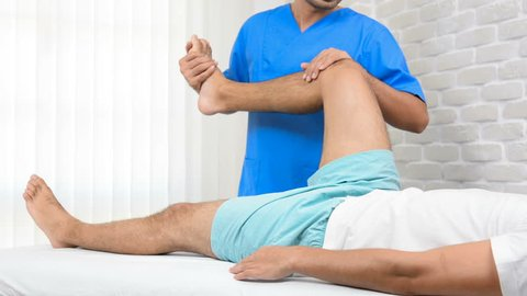 Physiotherapist stretching male patient on the bed in hospital - physical therapy concept