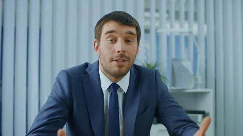 Handsome Respectable Businessman Sitting at His Desk, Talking into the Camera, Charismatically Gesturing. Shot on RED EPIC-W 8K Helium Cinema Camera.