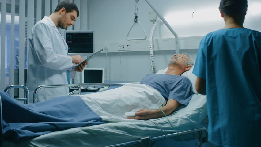 In the Hospital Sick Man Rests, Lying on the Bed, Doctor and Nurse Enter Ward and Check up the Patient. Recovering Man Sleeping in the Modern Hospital Ward. Shot on RED EPIC-W 8K Helium Cinema Camera. | Shutterstock HD Video #1009728701