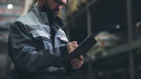 Storekeeper in the warehouse make an audit and an inventory. Man at a large storage, looks around, finds a box and takes notes. Modern man with a beard is dressed in gray uniform, works in a warehouse