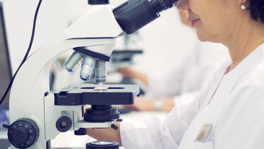 A female scientist is working in a laboratory with a microscope #1009751951