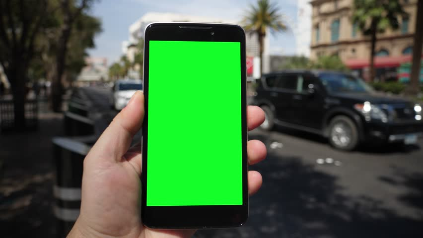A man holds a smartphone outside near Las Vegas Boulevard as traffic and taxis pass by in the background. Green screen with optional corner pin markers for advanced screen replacement.   | Shutterstock HD Video #1009768931