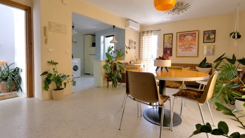 Malaga, Spain.Circa March 2018. Real estate virtual tour. Camera fly-through the interior of a retro decorated home. Vintage living room and kitchen.