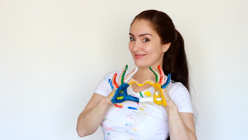 Girl painter student smiles and shows the heart. Love of art and profession. Dirty clothes and dirty hands of the artist woman. | Shutterstock HD Video #1009823891