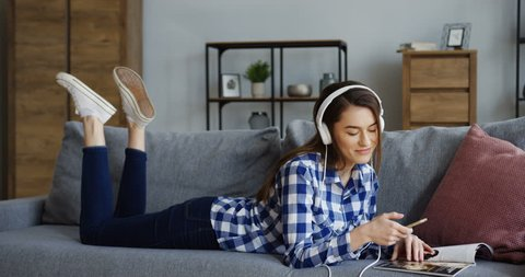 Young charming woman flipping a fashion magazine pages and listening to the music on the smartphone device while lying on the couch in the cozy living room. Inside