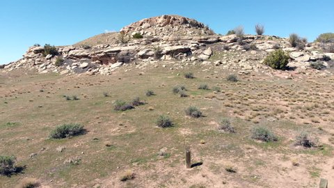 Aerial footage captured by a drone rising over a desert hill in Colorado, near Utah.