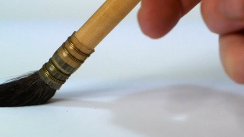close up of a hand who is painting with a brush for gilding white background