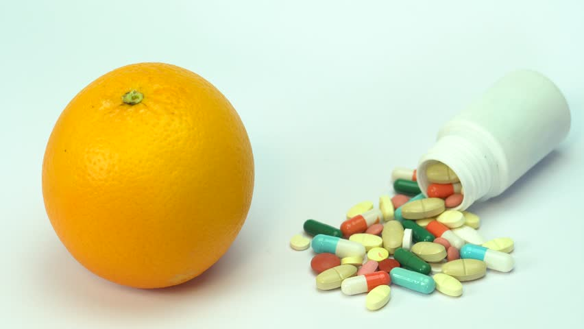Close up of orange fruit and pills isolated - vitamin concept | Shutterstock HD Video #1009841861