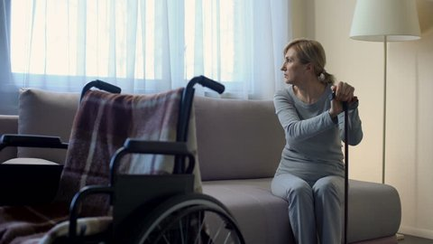 Sad retired lady waiting for husband at hospital, looking at wheelchair, rehab