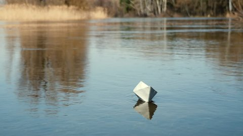 A paper boat is floating on the water. Origami boat floats away into the distance along the river
