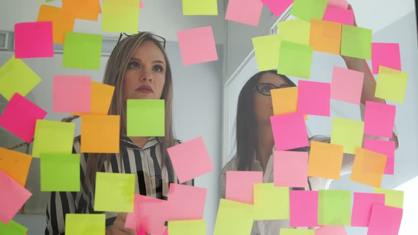Creative business team brainstorming ideas working together sharing data late at night after hours in modern glass office. Two very beautiful girls in office clothes blonde and brunette with glasses | Shutterstock HD Video #1009887071
