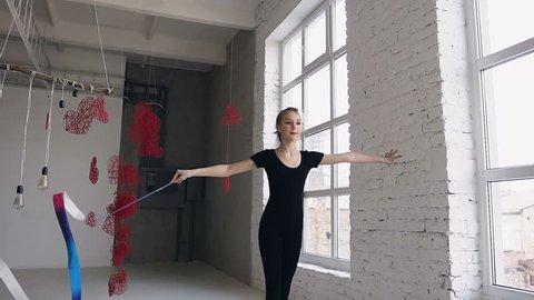 Attractive teenage girl gymnast dancing with colored ribbon in sport gym in white background near windows. Attractive girl gymnast jumping with ribbon in sport school, slow motion