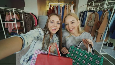 Point of view shot of two attractive careless girls making selfie with paper bags in women's clothes shop. Friends are posing, laughing and chatting happily