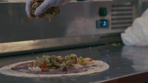 Slow motion shots of a cook making tortilla wraps. Taco, burrito, quesadilla