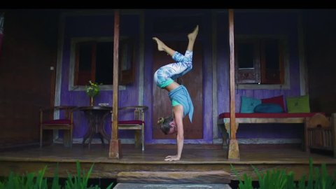 Woman in yoga sports clothing doing handstand yoga asana in front of a wooden house in bali