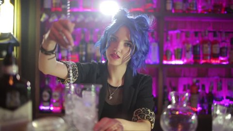 female bartender. girl with blue hair. cocktail making in night bar