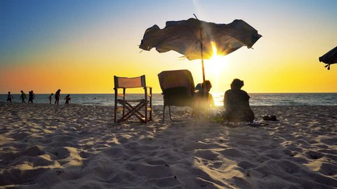 Undefined silhouette of senior couple of old man and woman sitting on the beach watching sunset