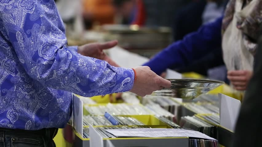 Customers choose vinyl records in the store, close up hands view