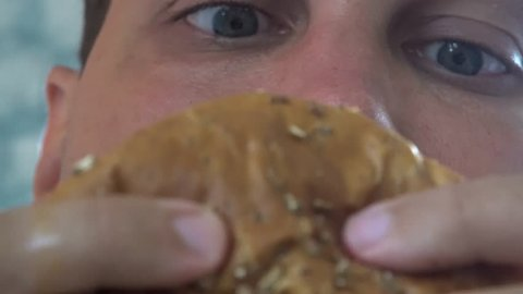 Hungry Man Eating Burger with Appetite and Greed. Gluttony and Obesity Concept. Close Up