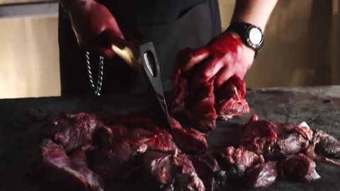 Mad scary caucasian bearded butcher man in bloody apron chops red meat with axe and bites on it in abandoned building
