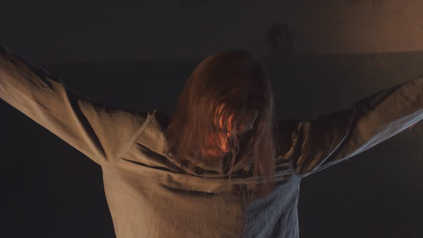 Insane long haired caucasian man with straitjacket sleeves tied to ceiling, dust falling on his head in abandoned building