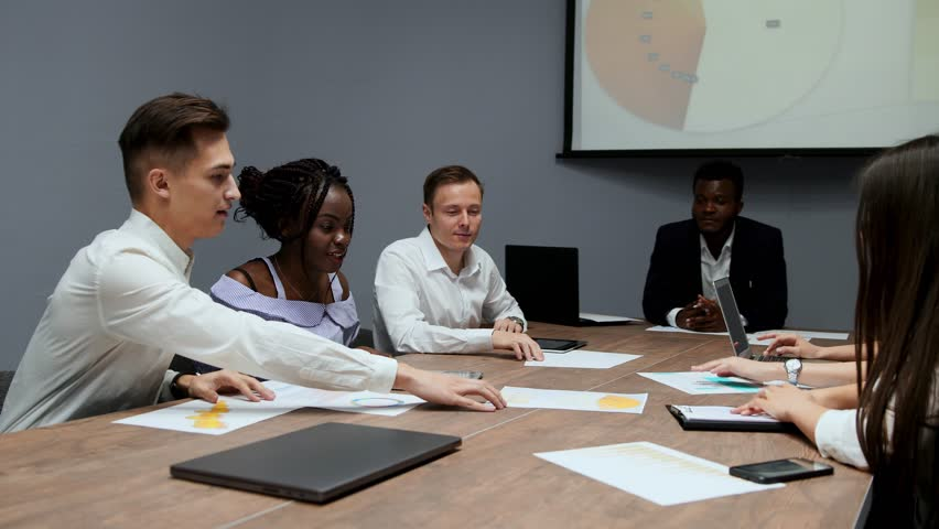 A group of creative multi-ethnic managers disassemble at the meeting of the board of directors in the conference hall the graphs of profit for the last year in the firm. An African American girl and a   Shutterstock HD Video #1009936061