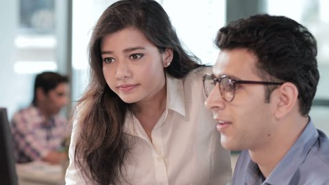 a young and beautiful office girl smiling while working with a handsome male colleague. A young and happy office team working together on a business/ financial project in a busy corporate office