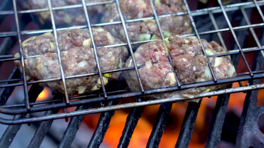Closeup of uncooked, raw kofta in a grilling basket on a hot grill with fire and smoke. | Shutterstock HD Video #1009993661