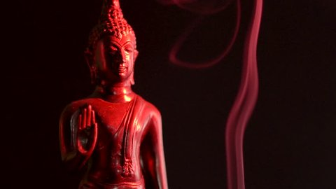 Buddha bathed in red light sliding to the left as smoke rises.