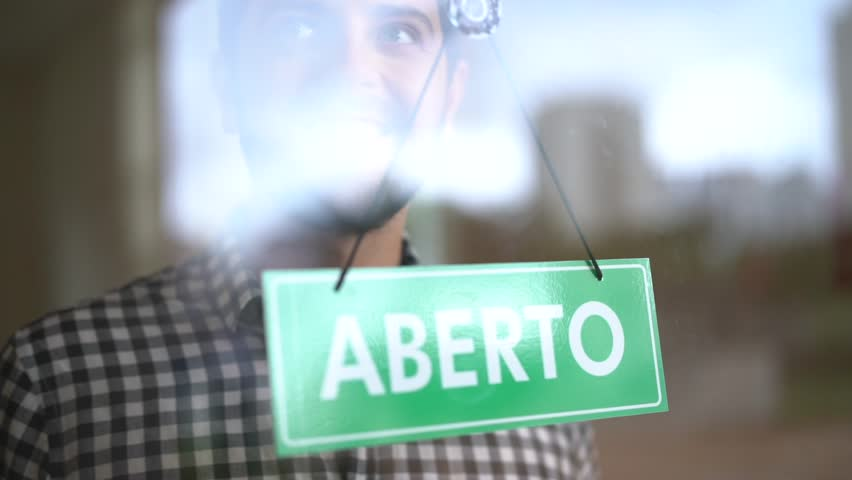 Business owner turning as open (Aberto in portuguese) for business sign in their storefront window