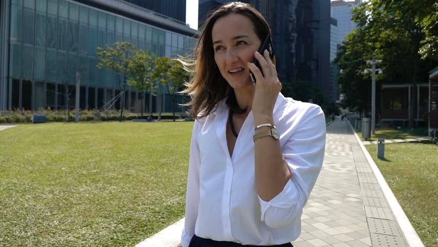 Happy businesswoman talking on cellphone walking in city, super slow motion 240fps  | Shutterstock HD Video #1010027021