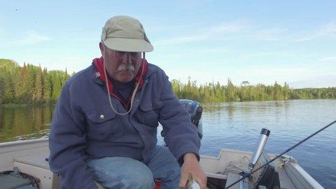 fisherman puts his walleye into live well 4k gimbal