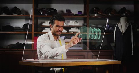 A man in a tailor shop, he clicks a glass monitor to select the material and the type of shirt to be bought with the holography. Concept of: future, technology and tradition.