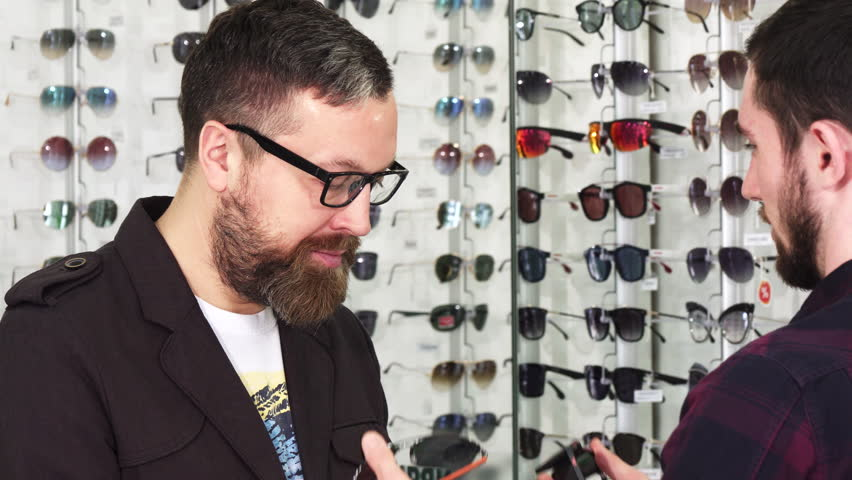 Professional optometrist showing glasses for sale to his male customer   Shutterstock HD Video #1010067521