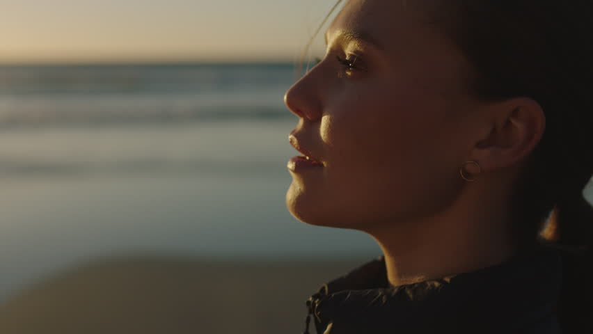 Close up portrait of beautiful young woman enjoying calm peaceful sunset looking relaxed pensive caucasian female on ocean seaside beach | Shutterstock HD Video #1010077781
