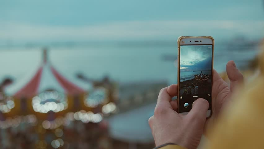 Close up shot of the man's hands, holds a mobile phone and takes pictures on a portable gadget, a teenager works as a blogger in social networks and shoots children's carousels | Shutterstock HD Video #1010095511