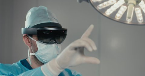 CU Portrait of surgeon using augmented reality holographic hololens headset while operating in modern operation theater. 4K UHD 60 FPS SLO MO