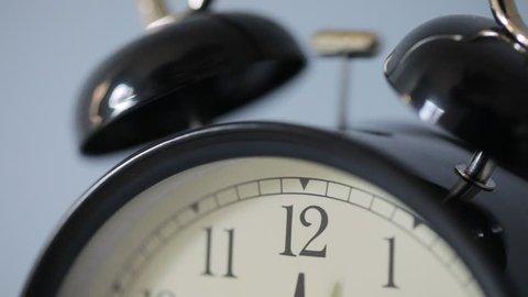 Vintage clock ringing on isolated white background slow motion