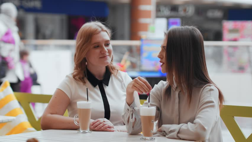 Young women drinking coffee and communicating in cafe. | Shutterstock HD Video #1010135021