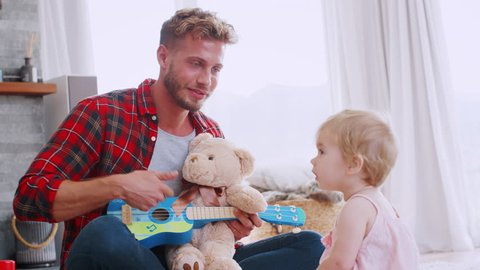 Young dad playing ukulele with toddler daughter, close up