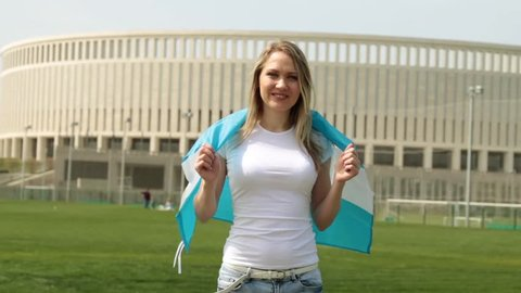 Woman sporting a fan with the Argentine flag. Woman with the flag of Argentina.