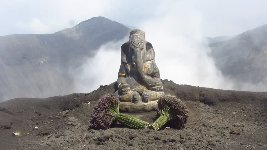 Smoke rising behind a statue of Ganesha at the caldera of the active volcano Mount Bromo in Java, Indonesia.