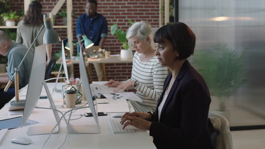 Mature mixed race business woman using computer in diverse modern office workspace colleagues working on corporate project creative multi ethnic team | Shutterstock HD Video #1010156981