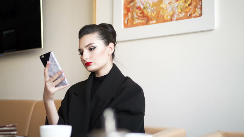 Young girl in the restaurant. Business woman uses the smartphone. | Shutterstock HD Video #1010172581